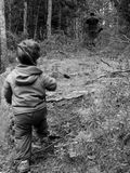 Father and Son Hunting. In the woods, father has gun, son has stick Stock Photo
