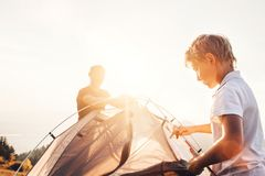 Father and son install touristic tent for camping