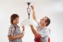 Father and son installing a ceiling lamp. And fluorescent lightbulb together stock photography