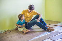 Father and son installing new wooden laminate flooring. infrared royalty free stock image