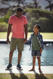 Father and son interacting while holding hands near poolside Stock Photos