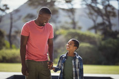 Father and son interacting while holding hands. Smiling father and son interacting while holding hands on a sunny day Stock Photo