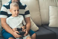 Father with son with joystick controllers in hands. Father and son holding a joystick controllers while playing a video games at home Royalty Free Stock Photography