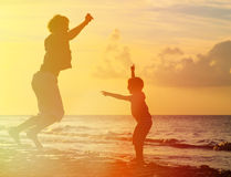 Father and son jumping at sunset Stock Photos