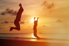 Father and son jumping at sunset beach Royalty Free Stock Images