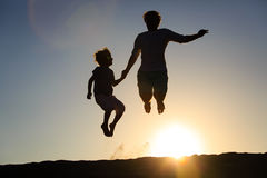 Father and son jumping at sunset Stock Photography