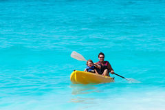 Father and son on kayak ride in tropical ocean Royalty Free Stock Images
