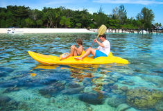 Father and son kayaking next to tropical coral island Stock Images