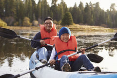 Father and son kayaking on a rural lake, front view Stock Photos
