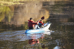 Father and son kayaking together on a lake, back view stock photos