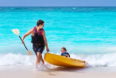 Father and son kayaking together on tropical beach Stock Photo