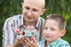 Father and son keeping in their hands wendy house Stock Image