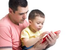 Father and son kid play with tablet computer indoors Stock Image