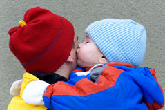 Father and son - the kiss. A little boy embrace and kisses his father in a cold winter day - adorable family moment Royalty Free Stock Photography