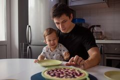 Father and son in the kitchen. kid wants a delicious hot cake. Young men with son, happy family stock photo