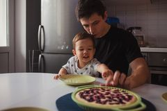 Father and son in the kitchen. kid wants a delicious hot cake. Young men with son, happy family royalty free stock photos