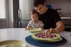 Father and son in the kitchen. kid wants a delicious hot cake. Young men with son, happy family stock image