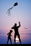 Father and son with kite at sunset Stock Photo