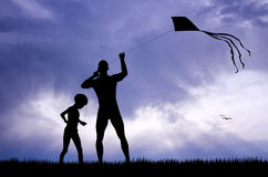 Father and son with kite at sunset Stock Image