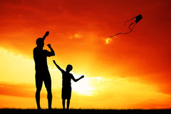 Father and son with kite at sunset Royalty Free Stock Images