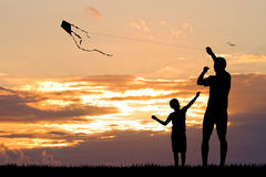 Father and son with kite at sunset Stock Photos
