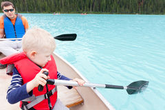 Father and son on a lake. Father and his son paddling on a canoe Royalty Free Stock Photos