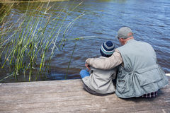 Father and son at a lake. In the countryside Royalty Free Stock Image