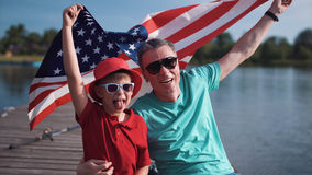 Father with son on lake. Father with son holding American flag and sitting on a pier near water celebrating 4th July or Fathers day Stock Photography
