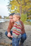 Father and Son at the Lake. A little, blond, boy, wearing a striped sweater, at the lake with his dad exploring Royalty Free Stock Photography