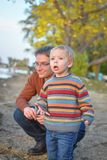 Father and Son at the Lake. A little, blond, boy, wearing a striped sweater, at the lake with his dad exploring Royalty Free Stock Image