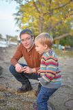 Father and Son at the Lake. A little, blond, boy, wearing a striped sweater, at the lake with his dad exploring Royalty Free Stock Photos
