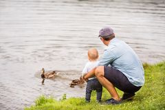 Father and the son by the lake in summer. Father and the son spending time together outside in green nature Royalty Free Stock Photo