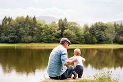 Father and the son by the lake in summer. Father and the son spending time together outside in green nature Stock Photo