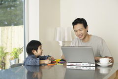 Father And Son With Laptop And Colors At Table Stock Photo