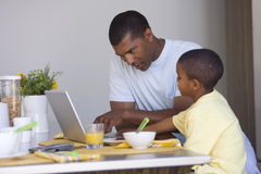 Father and son (7-9) at laptop computer Stock Image
