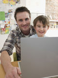 Father And Son With Laptop Sitting At Table Stock Photo