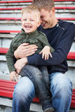 Father and son laughing in empty stadium Royalty Free Stock Photos
