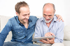 Father and son laughing. Father and son looking at device Stock Photos