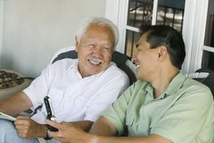 Father and son laughing outside home Stock Photos