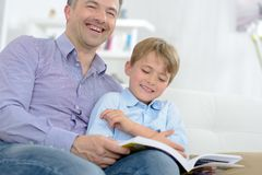 Father and son laughing while reading book. Father Stock Images