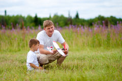 Father and son launch plane model in summer stock photo