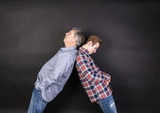 Father and son lean on back to back Royalty Free Stock Photo