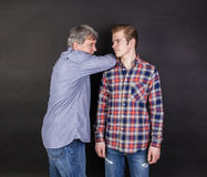 Father and son lean on back to back Stock Images