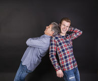 Father and son lean on back to back Royalty Free Stock Photos