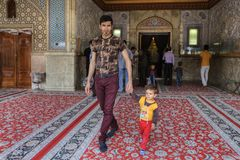 Father and son leave the mosque after prayer, Shiraz, Iran. Fars Province, Shiraz, Iran - 19 april, 2017: Shah Cheragh Shrine,  man comes out of the mosque with Royalty Free Stock Photos