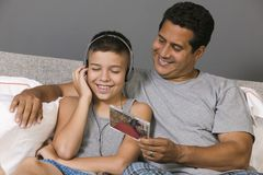 Father and Son listening to Music sitting on bed Royalty Free Stock Photo