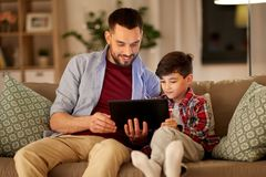 Father and son listening to music on tablet pc royalty free stock image