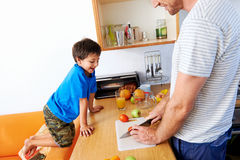 Father and son. A little boy watching his father cut up fruit and vegetables in the kitchen royalty free stock photo