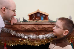 Father and son look at each other near fireplace Stock Photos