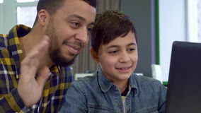 Father and son look at the laptop screen stock video footage